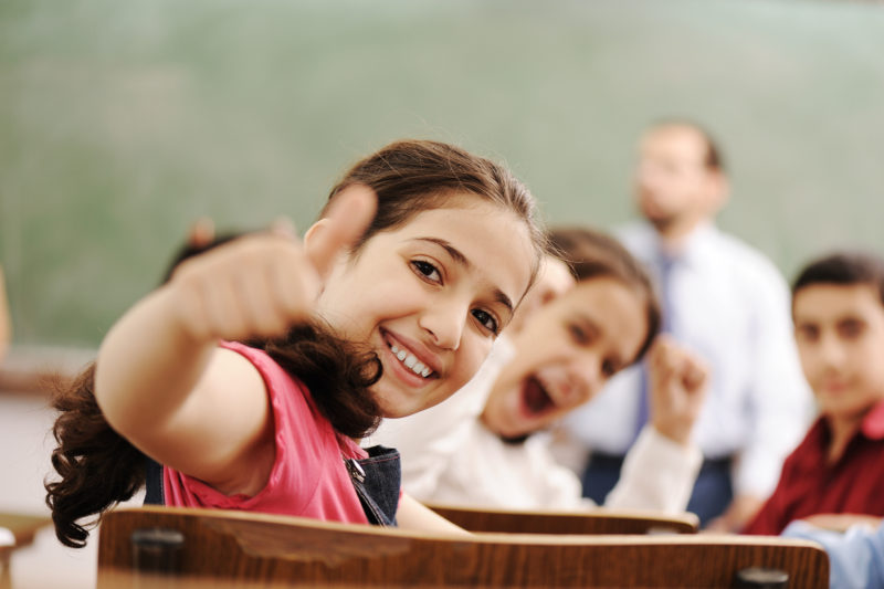 Happy children smiling and laughing in the classroom, showing thumb up, successful pupils and teacher